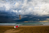 Storm approaching Manly with surfboard and sign