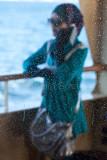 Woman through salt sprayed ferry window