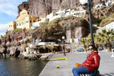 Landlubber relaxing at the Santorini Harbor, with medieval fortress looming large in the background.