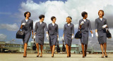 1965 - Delta stewardesses modeling their uniforms on the ramp east of Concourse 1 (now H) at Miami International Airport