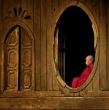 Novice seated in an oval teak wood window