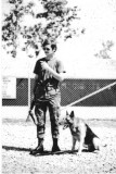 A1C Mark Smoot & Jake-0X14 at the kennels.  I'm the one with the CAR-15. April 1972