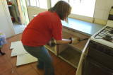 Tracy demolishing a kitchen cupboard