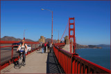 Bikers , walkers and traffic on the Golden Gate  Bridge and river traffic  below.