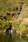 Small waterfall leads into large pool near rock biv