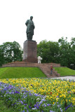 View with flowers of the monument located in a park across from the Red Building.