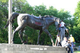 Statue of a horse in the park with kids climbing on it.
