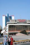 People, a modern sculpture and the Marine Station building at the Odessa pier.