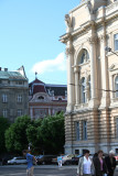 Corner view of Franko Lviv University with people strolling around in front of it.