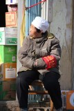 Old Chinese woman sitting in front of a shop in Beijing.