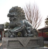 Close-up of guardian lion. It is a male lion because his paw rests on a ball.