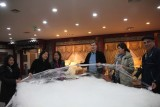 I am with people on my tour holding up the raw silk.
