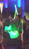 A boy and girl with green light sabers.
