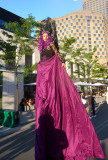 A chic woman on stilts with a rose dress and hair. She looked a bit like Cher.