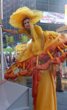 A yellow-clad woman on stilts looked like she was going to Cinderella's ball.