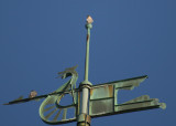 Peregrines: one atop top weathervane bulb: other upper fore spar