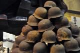 Rusting German steel helmets stacked on top of rubble