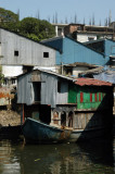 An old houseboat with what look like squatters shacks built on top of it