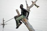 Boy sitting on tree trunk