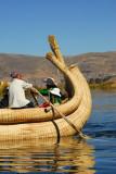 Uros man paddling a reed boat