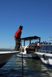 Crew member poling the boat alongside the pier
