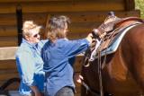 zP1010835 Dora a Montana rancher and farmer watches wrangler adjust saddle.jpg
