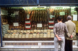 A Sevilla couple contemplates a display of hams, cheeses and wines
