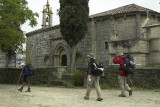 Pilgrims pass a 12th C. church at Melide, Galicia