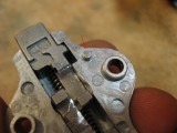 Notice that the small stud lines up with the hole below when reassembling latch
