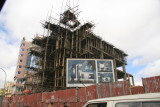A new, seemingly high-tech building under construction using decidedly low-tech means.