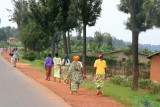 Women dressed in colorful outfits walk by the well-maintained paved road from Kigali to Ruhengeri