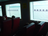 VIEW OUT THE SIDE WINDOWS OF THE FERRY WITH NOVA SCOTIA DISAPPEARING IN THE BACKGROUND