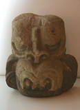 A primitive stone carving of an animal head.