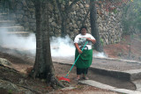 This woman was sweeping up pine needles and burning them.