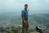 A picture of me in Parque Naciones Unidas pointing to the view of Tegucigalpa below.
