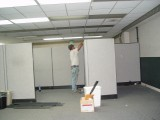 ONE OF THE FACTORY EMPLOYEES DISMANTLING A DIVIDER IN ONE OF THE OFFICES