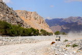 Another jeep approaches along the dusty wadi