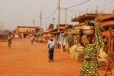 Woman in a colorful dress carrying a load on her head, Abomey