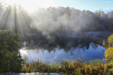 Rising sun through pond smoke on a frosty morning