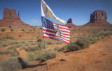 The Navajo Flag Flies Above A Flag Honoring Geronimo At Monument Valley