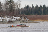 Vehicle being carried to Moose Factory on small barge.