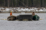 Two canoes move a small barge.