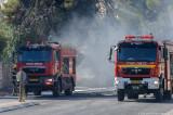 Burned-out car between fire trucks