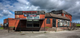 An unfortunate ailing estate pub, gradually being vandalised into oblivion.