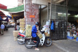 A motorcyclist with a heavy load about to take a shortcut through the indoor part of the market - Hanoi, Vietnam