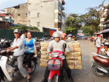 Street near the main market. Workers often carry heavy loads on their motorcycles as seen here - Hanoi, Vietnam