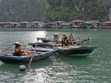 Boats in Ha Long Bay, Vietnam - a floating village is in the background