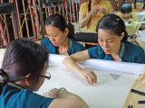 Artisans embroidering a table cloth at the Thang Loi Company, Hoi An, Vietnam
