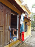 Woman cleaning the front entrance of her house - next photo shows bird cages seen here - Old Town, Hoi An, Vietnam