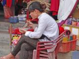 Shopkeeper on lunch break outside her shop - Old Town, Hoi An, Vietnam
